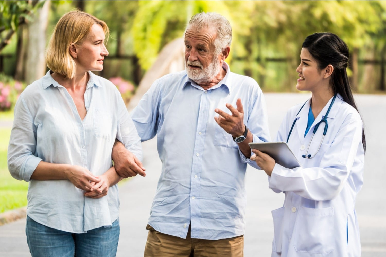 Compare health insurance: couple walking with medical professional