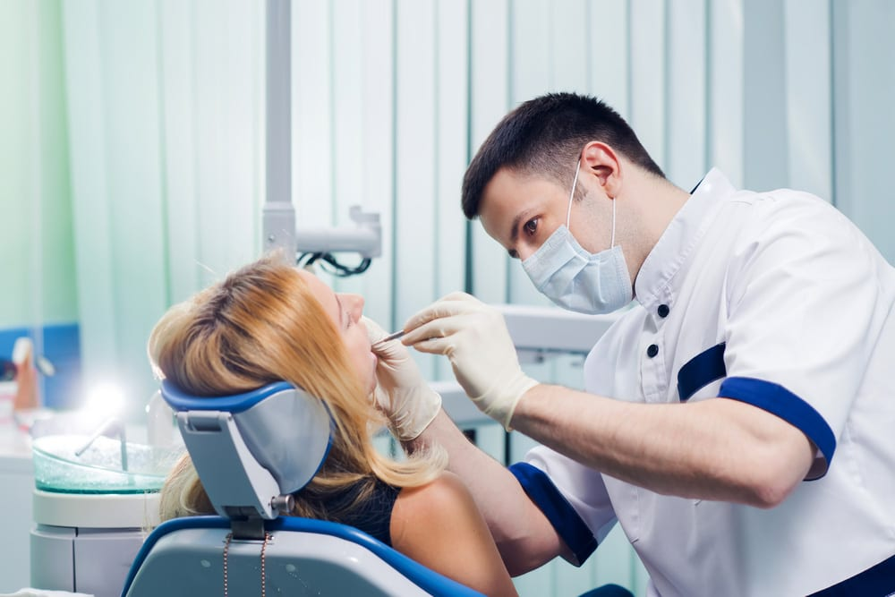Dentist performs a dental check up on a woman: health insurance comparison